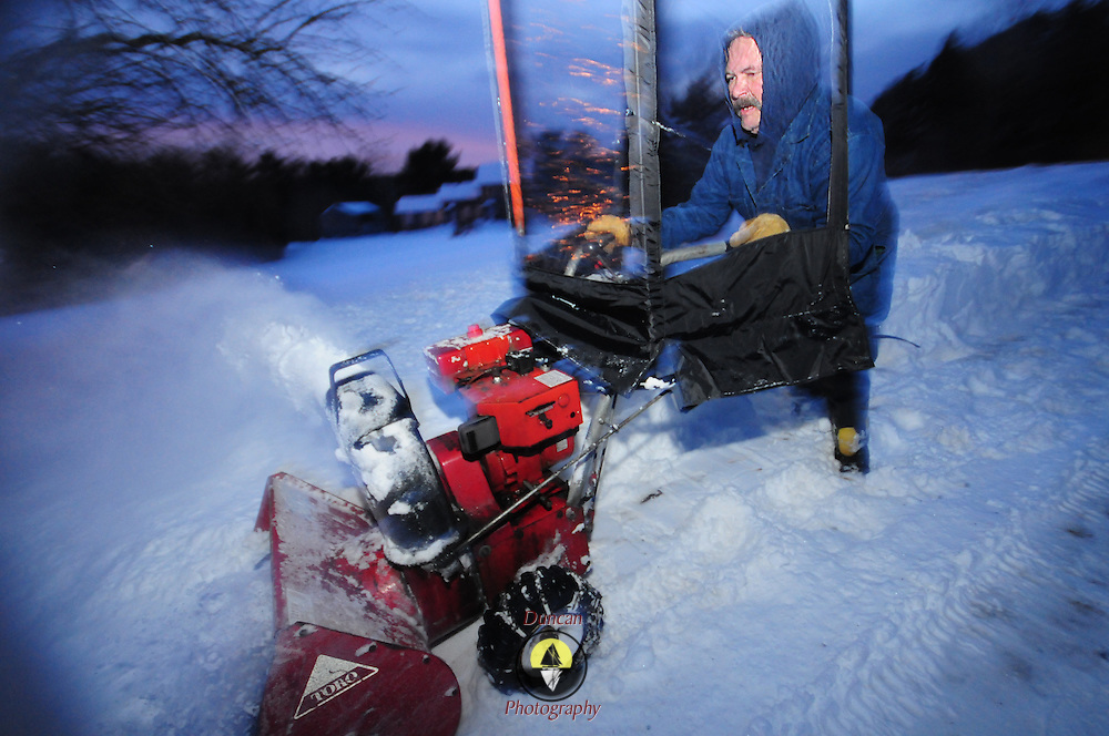 12/22/08 -- BATH, Maine.  Rusty Johanson fights a rough patch of dirt and rock as he snowblows a trail behind his home in Bath on Monday evening across a field near where his mother lives. Bath received over 18 inches of snow on Sunday's storm. Photo by Roger S. Duncan.