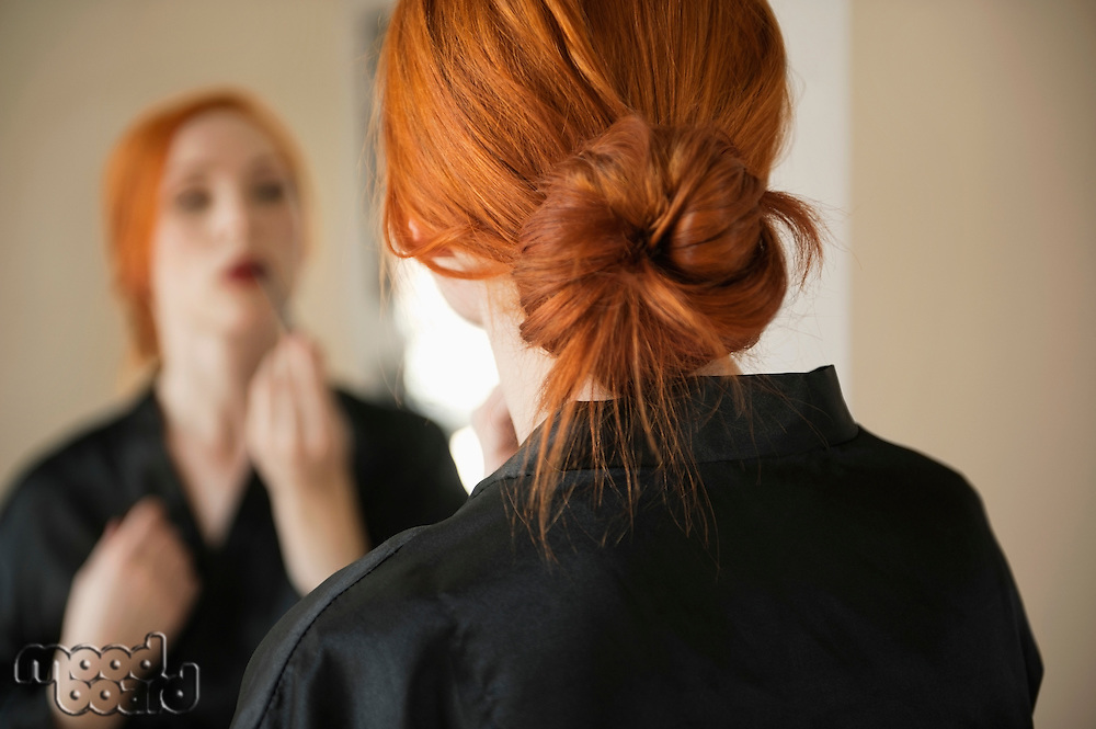 Back view of young woman applying makeup