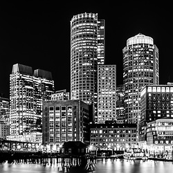 Boston panorama cityscape at night black and white photo with the Boston waterfront, downtown Boston skyline and Northern Avenue Bridge. Boston Massachusetts is a major American city in the Eastern United States of America. Panoramic photo ratio is 1:3.