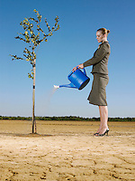 Businesswoman watering tree in desert full length