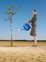 Businesswoman watering tree in desert full length
