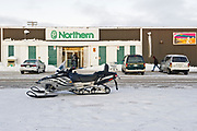 Snowmobile and vehicles in front of Northern store on main street isolation