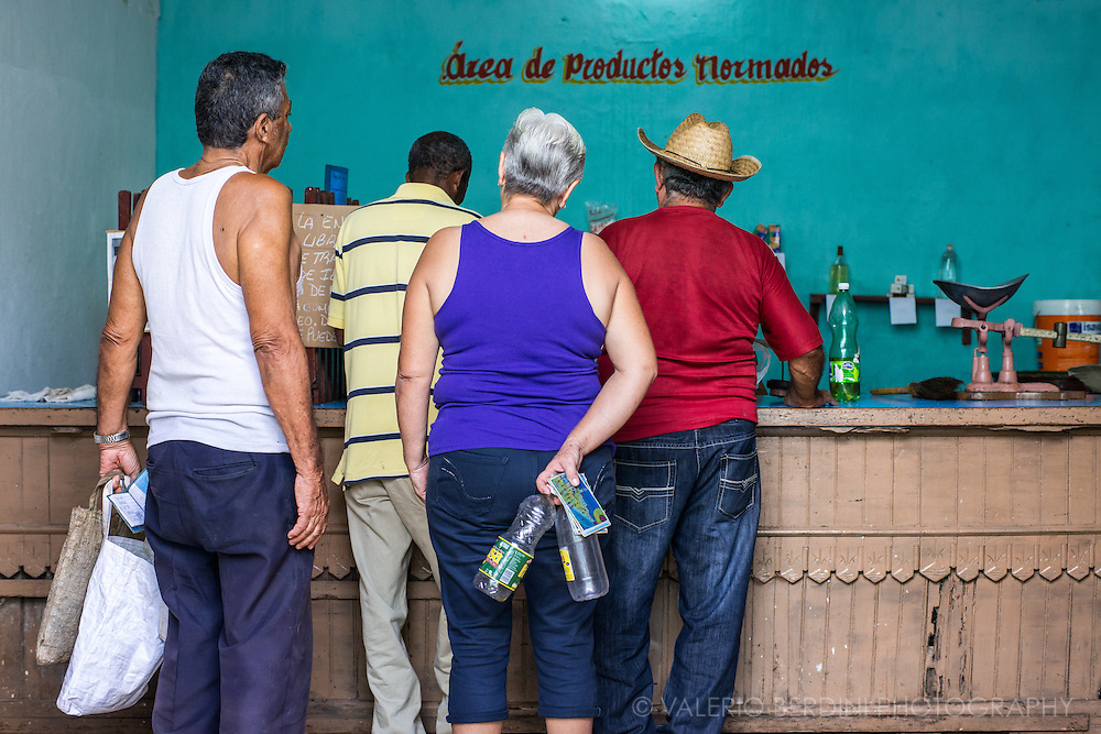 People queuing with empty bottles and bags to get their ratio of oil, rice, sugar and flour (producto normados). Each has to take the supplies booklet (Libreta de Abastecimiento) in order to cross the monthly amount each Cuban is allowed to get. Remedios. Cuba, 2015.