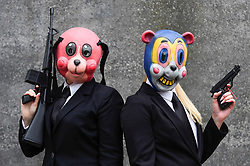 © Licensed to London News Pictures. 25/10/2019. LONDON, UK. Women dressed as (L to R) Hazel and Cha Cha from the Umbrella Academy TV show join other cosplayers from all over the world attending the opening day of the bi-annual MCM Comic Con event at the Excel Centre in Docklands.  The event celebrates popular culture such as video, games, manga and anime providing many attendees with the opportunity to dress up as their favourite characters.  Photo credit: Stephen Chung/LNP