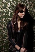 Peaches Geldoff posing and leaning against green and white floral wallpaper.