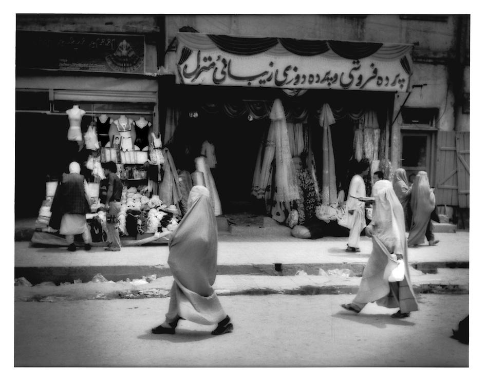 Women wearing burkhas pass shop selling lingerie near the Kabul River, Afghanistan.