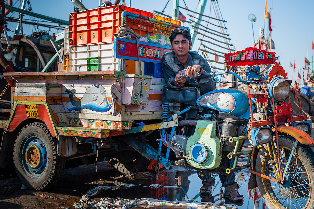 Young man on motorbike with cart on harbor dock in Diu (India)