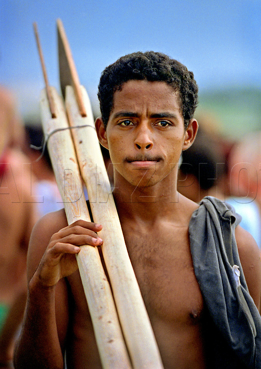A young Cuban rafter holding homemade oars anticipates his voyage on a homemade raft off the coast of Cojimar, Cuba. In 1994 Cuban balseros turned the tiny fishing village of Cojimar into a major point of embarkation for thousands seeking a better life. The mass exodus led to the 'Wet-foot, Dry-foot' United States Immigration Policy.