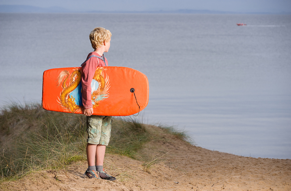 Boy with board beside the sea, Roseisle, Aberdeenshire and Moray Forest District, Forestry Commission Scotland