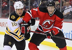 Jan 4, 2012; Newark, NJ, USA; New Jersey Devils defenseman Henrik Tallinder (7) and Boston Bruins right wing Nathan Horton (18) battle for the loose puck during the first period at the Prudential Center.