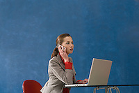 Business woman using mobile phone and laptop in office