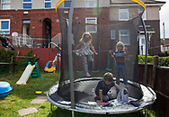 McKenzie (6), Lucas (5), Regan (5), read int their trampoline at home in Shefield UK Tuesday, Aug. 12, 2014The D'Arby family is involved in the FAST  (Families and Schools Together) program which encourages parents to read to their children at home.(Elizabeth Dalziel for Save the Children )