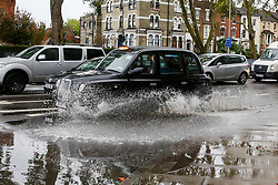 © Licensed to London News Pictures. 17/10/2019. London, UK. A taxi drives through a flood on Tottenham High Road after heavy downpour in north London this afternoon. Photo credit: Dinendra Haria/LNP