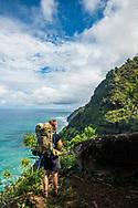 A hiker on the Kalalau Trail on the Na Pali Coast of the north shore of Kauai, Hawaii.