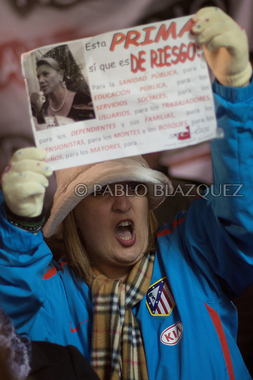 A woman holds a placard and shouts slogans outside the local healthcare centre which closes at 8pm tonight its emergency hours on January 14, 2013 in Tembleque, near Toledo, Spain. A total of 21 centres, specially in rural areas, in the region of Castilla-La Mancha, are eliminating emergency hours services following budget cuts and privatisations in Spanish health services.
