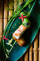 A sampler dish of Vietnamese spring rolls served on a banana leaf.