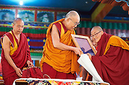 Namdol Phuntsok (best results at Geshema examination) from Kopan Nunnery after reading out a citation of gratitude to His Holiness and presented him with a framed copy illustrated and printed in traditional ornamental style of gold on blue at Drepung Lachi Monastery in Mundgod, Karnataka, India on December 22, 2016