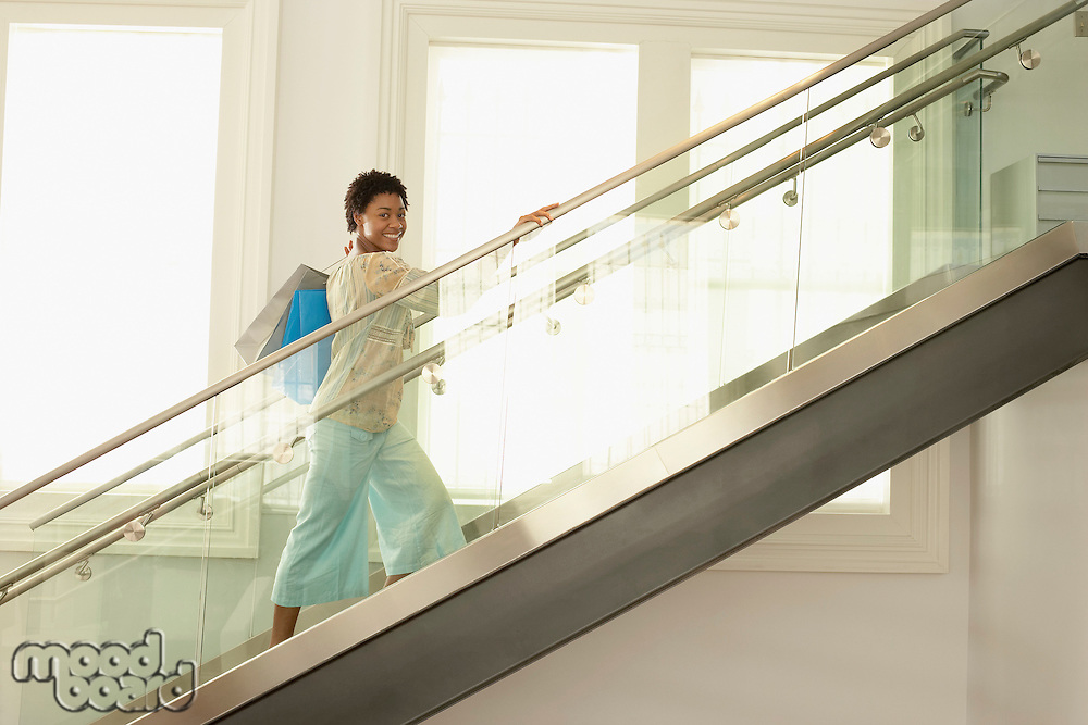 Woman walking up the modern stairs with shopping bags portrait