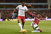 Aston Villa striker Jonathan Kodjia (26) flys in to tackle Nottingham Forest midfielder Tendayi Darikwa (27) during the EFL Sky Bet Championship match between Aston Villa and Nottingham Forest at Villa Park, Birmingham, England on 28 November 2018.