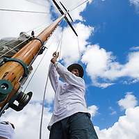 An unidentified crew member prepares to hoist the main sail on board SY Galatea during the 2008 Antigua Classic Yacht Regatta . This race is one of the worlds most prestigious traditional yacht races. It takes place annually off the costa of Antigua in the British West Indies.