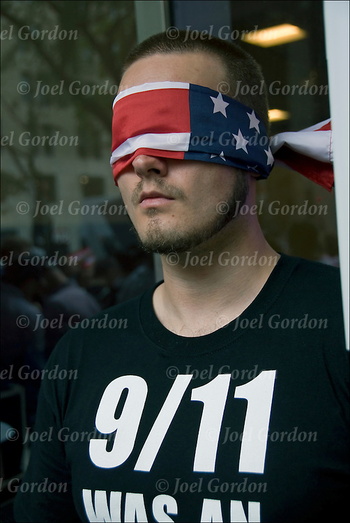 Conspiracy theory protester wearing an American flag (justice is blind) as a mask  covering his eyes,near ground zero on 9-11-11.<br /> <br /> 9/11 conspiracy theories question the official account of the events of September 11, 2001, and believe  inconsistencies in the official conclusions or some evidence that was overlooked.