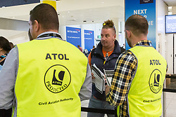 ATOL officials assist holiday makers at the Thomas Cook Check-in after the travel company ceased trading after failing to come to a deal with its bankers and creditors, leaving tens of thousands of travellers unable to depart on their holidays from South Terminal at Gatwick Airport, and a massive repatriation exercise to return holidaymakers from destinations all over the world. London Gatwick Airport, September 23 2019.