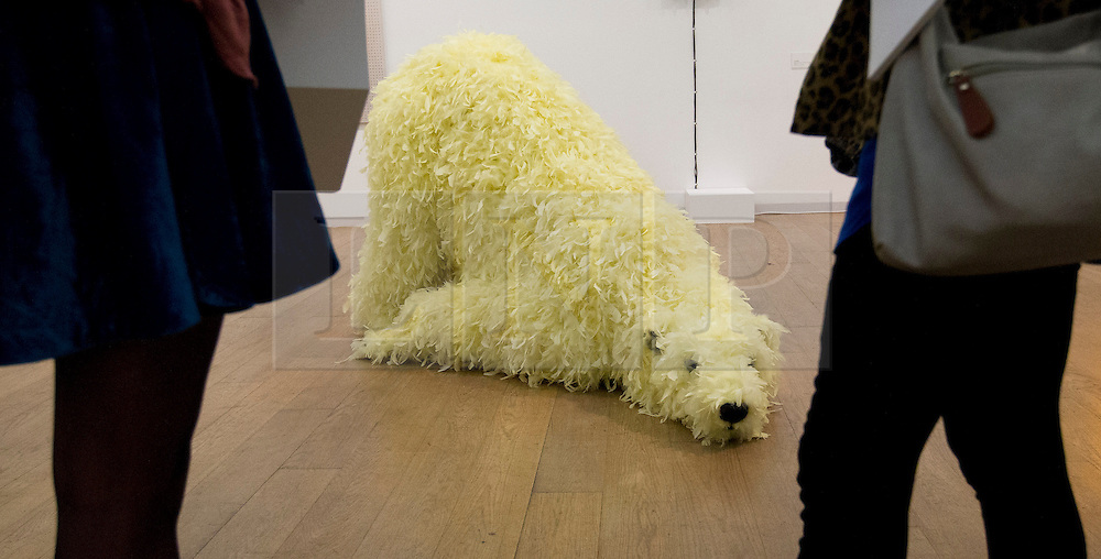 © Licensed to London News Pictures. 18/06/2013. London, UK. Paola Pivi's 'Have you seen me before?' (2008), a still life sculpture of a polar bear with fur made from chicken down, is seen through visitors at the press view for an exhibition entitled 'Have You Seen Me Before' at the Whitechapel Gallery in East london today (18/06/2013). The exhibition, containing works of art belonging to private collector Sandretto Re Rebaudengo, is on show at the gallery from the 18th of June to the 8th of September 2013. Photo credit: Matt Cetti-Roberts/LNP