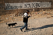 An elderly man walks his dog past a gang marker in memory of a slain member along a street corner where ten people have been killed in drug crimes in Juarez, Mexico January 15, 2009. The ongoing drug war has already claimed more than 40 people since the start of the year. More than 1600 people were killed in Juarez in 2008, making Juarez the most violent city in Mexico.