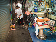 "06 FEBRUARY 2017 - BANGKOK, THAILAND:  A barber sweeps up her shop after giving a customer a haircut in what used to be known as Kalabok Market under the Phra Khanong Bridge in the Phra Khanong district of Bangkok. Kalabok is the Thai word for hairdresser and the market was called Kalabok because there were many barbershops and hairdressers under the bridge. In 1985, the city changed the name of the market to ""Singha Market."" There are still about 10 small men's barbershops, most with just one barber, and four women's salons, most with one hairdresser,  under the bridge.     PHOTO BY JACK KURTZ"