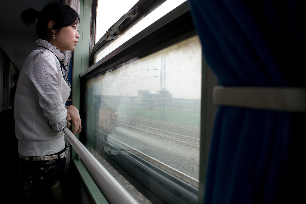 A young woman is looking through the window of the train to Beijing.