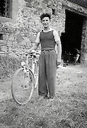 young adult man posing with his bicycle outside the barn