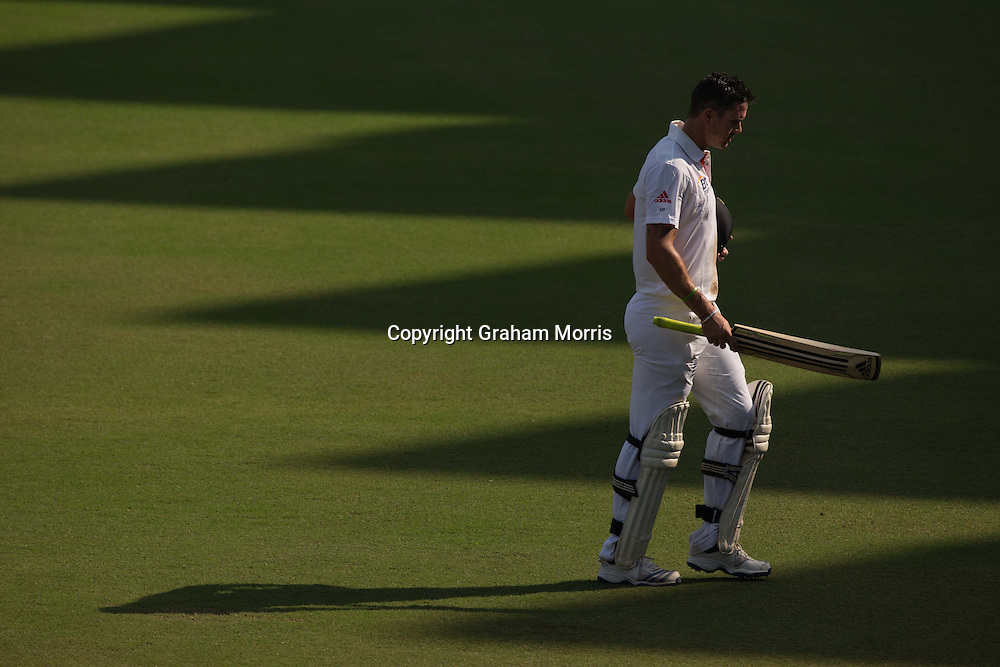 Kevin Pietersen walks off after being bowled by Pragyan Ojha (top) during the first Test Match between India and England in Ahmedabad.  Photo: Graham Morris (Tel: +44(0)20 8969 4192 Email: sales@cricketpix.com) 17/11/12