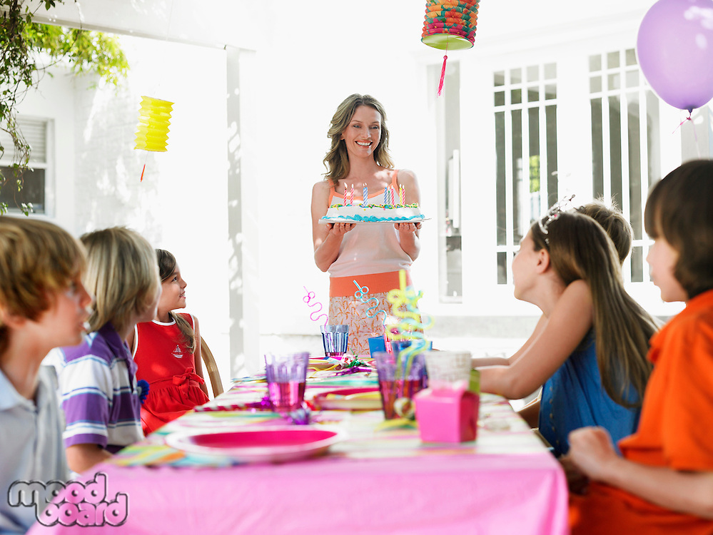 Mother serving cake to children (7-12) at birthday party