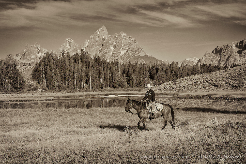 Cowboy Crossing the Meadow at Hedrick Pond in Jackson Hole, WY with the Grand Teton mountain range in the distance.