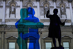 © Licensed to London News Pictures. 17/01/2018. London, UK. A statue of Sir Joshua Reynolds stands over a projection entitled 'Love Motion' by Rhys Coren' at the Royal Academy  Courtyard during the Lumiere London festival. Running from 18th-21st January 2018 more than 50 artworks are transforming the capital's streets, buildings and public spaces into an immersive nocturnal art exhibition of light and sound. Locations include King's Cross, Fitzrovia, Mayfair, West End, Trafalgar Square, Westminster, Victoria, South Bank and Waterloo. Photo credit: Peter Macdiarmid/LNP