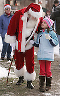 Sugar Loaf, NY - Santa Claus talks to a young girl while walking down the sidewalk of the crafts village of Sugar Loaf on Dec. 12, 2009.