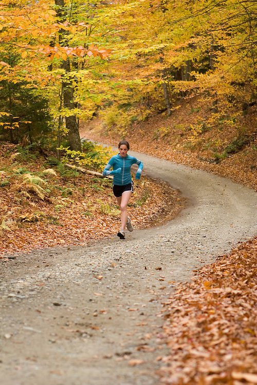 A woman runs on a back road through fall color in Vermont