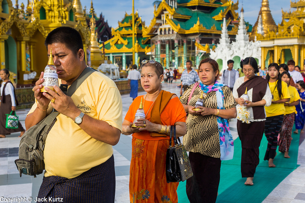 07 JUNE 2014 - YANGON, YANGON REGION, MYANMAR: People participate in a small private procession during a merit making ceremony for their company at Shwedagon Pagoda in Yangon. Shwedagon Pagoda is officially called Shwedagon Zedi Daw and is also known as the Great Dagon Pagoda and the Golden Pagoda. It's a 99 metres (325 ft) gilded pagoda and stupa located in Yangon. It is the most sacred Buddhist pagoda in Myanmar with relics of the past four Buddhas enshrined within: the staff of Kakusandha, the water filter of Koṇāgamana, a piece of the robe of Kassapa and eight strands of hair from Gautama, the historical Buddha.   PHOTO BY JACK KURTZ
