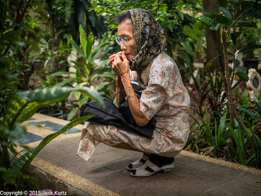 17 JULY 2015 - BANGKOK, THAILAND:     A woman prays at the grave of her parents in the cemetery of Ton Son Mosque after Eid services at the mosque in Bangkok. Eid al-Fitr is also called Feast of Breaking the Fast, the Sugar Feast, Bayram (Bajram), the Sweet Festival or Hari Raya Puasa and the Lesser Eid. It is an important Muslim religious holiday that marks the end of Ramadan, the Islamic holy month of fasting. Muslims are not allowed to fast on Eid. The holiday celebrates the conclusion of the 29 or 30 days of dawn-to-sunset fasting Muslims do during the month of Ramadan. Islam is the second largest religion in Thailand. Government sources say about 5% of Thais are Muslim, many in the Muslim community say the number is closer to 10%.          PHOTO BY JACK KURTZ
