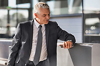 Mature businessman checking time on his wristwatch in airport