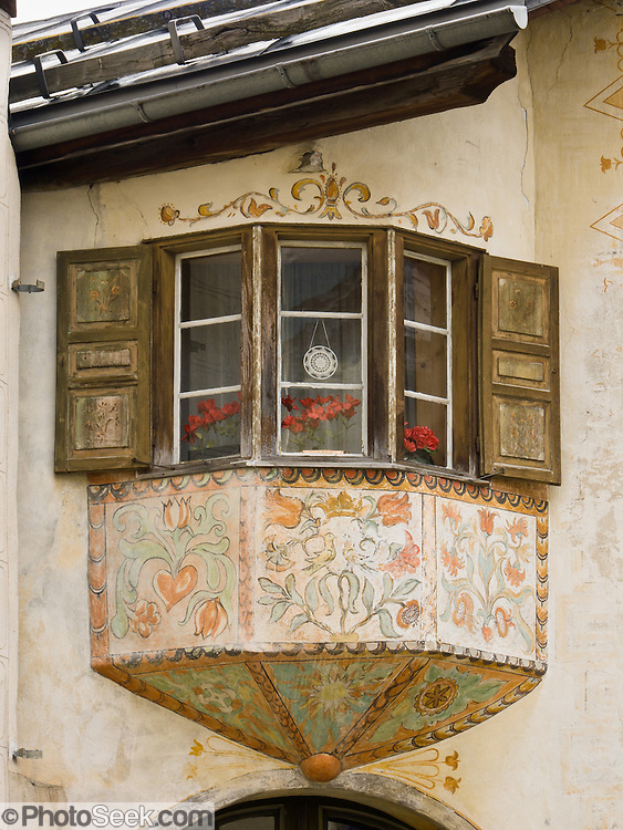 "Sgraffito (or scraffito, plural: sgraffiti) is a technique of wall decor where layers of plaster tinted in contrasting colors are applied to a moistened surface. Old wooden shutters frame a traditional window in the 17th century town of Guarda, in Graubünden canton, Switzerland, the Alps, Europe. Guarda is one of the best preserved and characteristic villages of the Lower Engadine. The Swiss valley of Engadine translates as the ""garden of the En (or Inn) River"" (Engadin in German, Engiadina in Romansh, Engadina in Italian). Published in Ryder-Walker Alpine Adventures ""Inn to Inn Alpine Hiking Adventures"" Catalog 2006-2009, 2011."