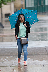 © Licensed to London News Pictures. 29/07/2018. London, UK.  A woman is caught in a heavy rain shower in central London near London Bridge station this morning.  Photo credit: Vickie Flores/LNP