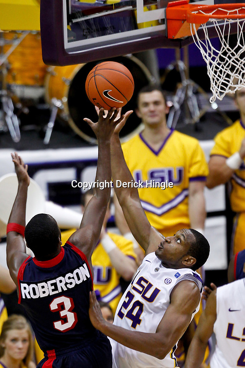 November 23, 2011; Baton Rouge, LA; South Alabama Jaguars guard Xavier Roberson (3) shoots over LSU Tigers forward Storm Warren (24) during the second half of a game at the Pete Maravich Assembly Center. South Alabama defeated LSU in overtime 79-75. Mandatory Credit: Derick E. Hingle-US PRESSWIRE