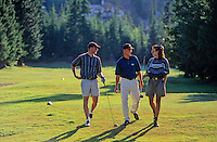 Three golfers enjoy a chat while walking a fairway of the Whistler Golf Course in Whistler, BC Canada.