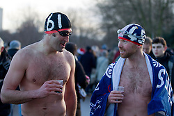 © Licensed to London News Pictures. 25/12/2013. London, UK. Two members of the Serpentine Swimming Club warm up with a glass of sherry after completing the Serpentine Swimming Club's annual Christmas morning 'Peter Pan Cup' race in Hyde Park, London, today (25/12/2013). The race, which takes place every Christmas Day on the Serpentine River, takes its name from from the novel by J.M.Barrie after the author presented the first Peter Pan Cup in 1904. Photo credit: Matt Cetti-Roberts/LNP