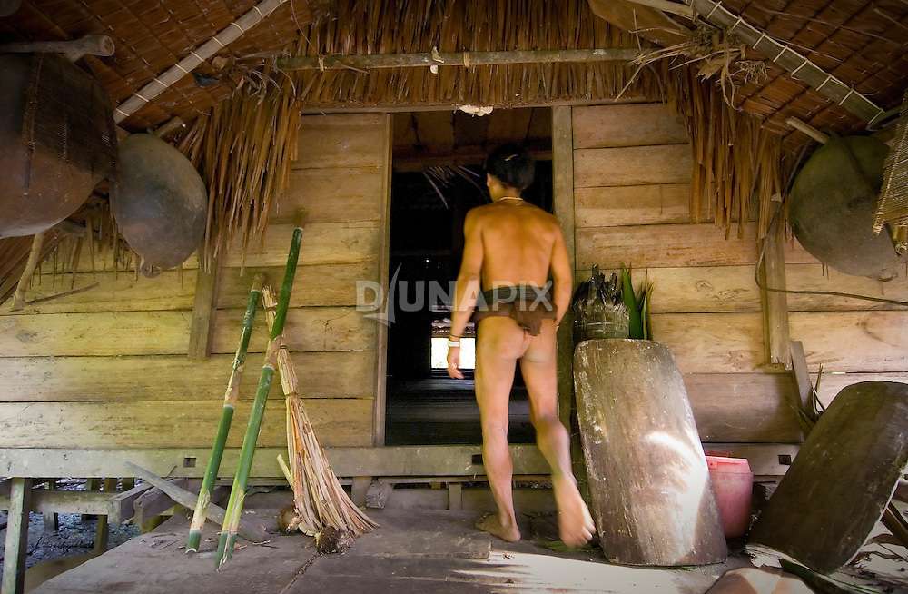 Teu Paksa, of Malagassat village, Siberut island, West Sumatra, walks into his traditional house (uma)