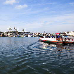 Photo of Balboa Island Ferry crossing Newport Harbor (Newport Bay) from Balboa Island to Balboa Peninsula in Newport Beach California. The Balboa Island Ferry has been operating since 1919 transporting people and vehicles.
