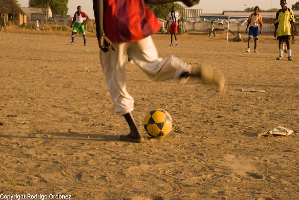 The goal keeper kicks off the ball during a football match in the town of Abyei.