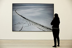 "© Licensed to London News Pictures. 14/03/2019. London, UK. A woman views a photograph of Cape Kamenny, Yamal Peninsula, Russia May 2018. <br /> Carmignac Photojournalism award - ""Arctic - New Frontier"" exhibition by Yuri Kozyrev and Nadir Vab Lohuizen on show at Saatchi Gallery. Yuri Kozyrev and Kadir van Lohuizen (NOOR) were awarded the 9th edition of the Carmignac Photojournalism Award dedicated to the Arctic. The endowment allowed them to carry out their pioneer double polar expedition 'Arctic: New Frontier'. <br /> The exhibition runs from 15 March, it will run until 5 May 2019 at Saatchi Gallery. Photo credit: Dinendra Haria/LNP"