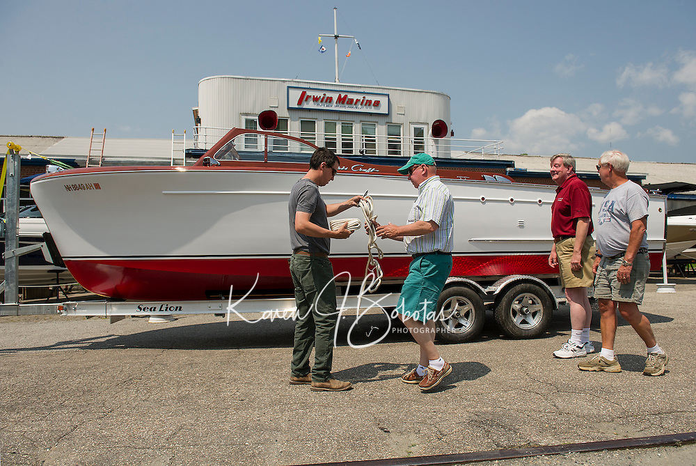 Seth and Gary Kiedaisch attach the bow and stern lines with Bruce Wright and Alan Lydiard as they prepare to launch their 1952 27' Chris Craft Cruiser into Paugus Bay at Irwin Marine on Friday afternoon.  The semi-enclosed cruiser has been fully restored over the past two years.  (Karen Bobotas/for the Laconia Daily Sun)